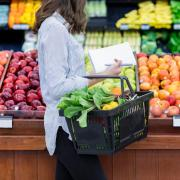 Woman holding a list and shopping basket at the produce section of a grocery store.