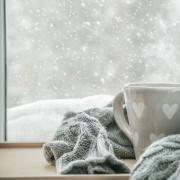 Cup of tea and blanket in front of snowy window