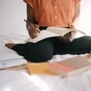 Person sitting cross-legged on their bed with an array of books in front of them, writing in a spiral notebook with a mechanical pencil.