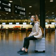 Young woman sitting on her luggage in an airport terminal.