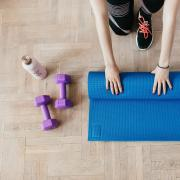 Person rolling up a yoga mat on the floor next to a water bottle and two dumbbells.