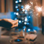 Two people holding sparklers together with a blurred background.