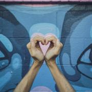 Person holding up their hands in a shape of a heart in front of a colorful outdoor mural.