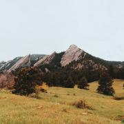 Photo of the flatirons in the fall with an eerie fog and overcast.