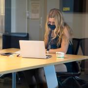 Grad student with long hair in a mask looking intently at her laptop.