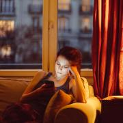 Girl sitting on her couch in the dark next to a lamp staring at her phone screen with a sad look on her face.