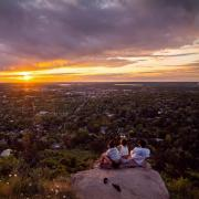 Three students sitting on a rocky hillside overlooking Boulder at sunset.