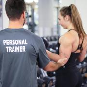 Male trainer working with female student on bicep curls