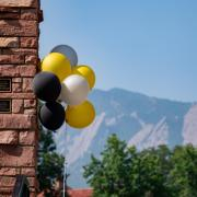 Yellow and black balloons floating near a building on campus in front of the flatirons.