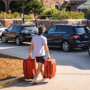 Student in mask carries two suitcases to a line of cars outside of Farrand Field.