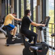 Two students riding stationary bikes on the top floor of the Rec Center.