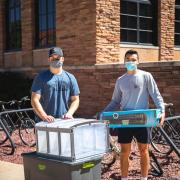 Two students in masks standing in front of a residence hall on move in day.