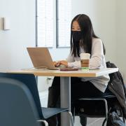Student wearing a mask sits at a campus table with her laptop and a coffee cup.