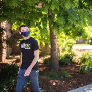 Two students in masks walking on campus.