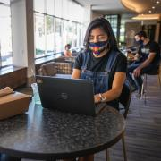 Female student wearing a mask working on her laptop.