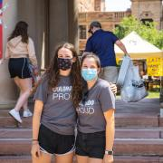 Two female students in masks standing in front of Sewall Hall wearing Colorado Proud t-shirts.