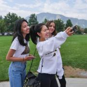Three students taking a selfie together in front of the flatirons by farrand field.