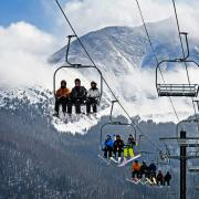 Photo of skiers and snowboarders riding a chairlift up a mountain.