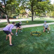Four students in masks playing spike ball on the grass.