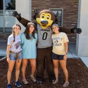 Three students standing in front of a residence hall with Chip the Buffalo.