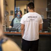 Staff member helping students in line at the UMC while wearing a mask behind a plexiglass barrier.