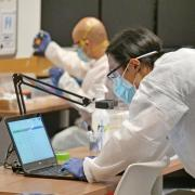 Health provider wearing a mask looks through a spreadsheet on his laptop.