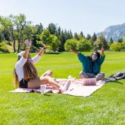 Three students sitting on blankets in front of the flatirons with their hands in the air laughing.