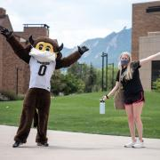 Chip the Buffalo standing with his arms raised next to a student in front of the Flatirons in Williams Village.