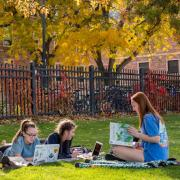 Three students sitting on a picnic blanket on Farrand Field with their textbooks and laptops.