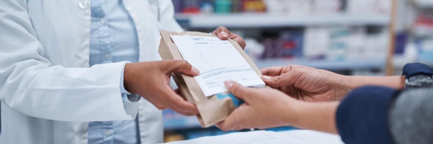 Pharmacist handing patient medications in bag
