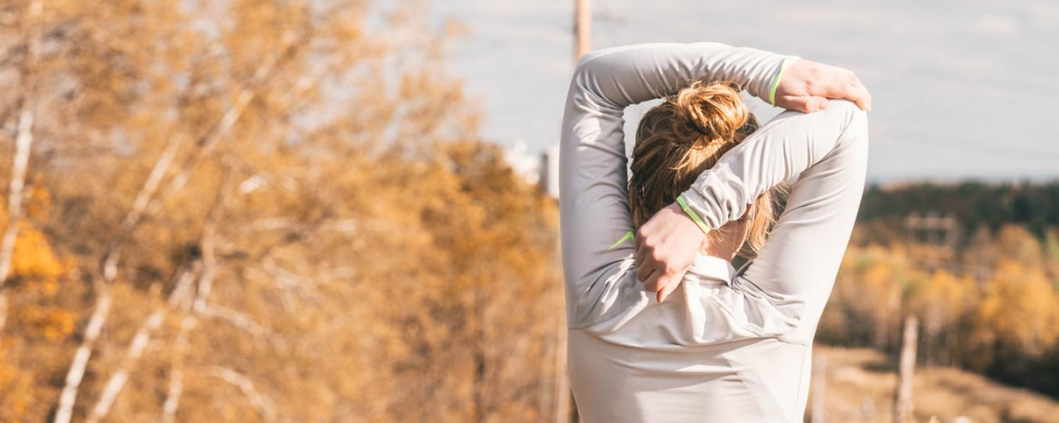 Women stretching shoulders before a run outside in fall