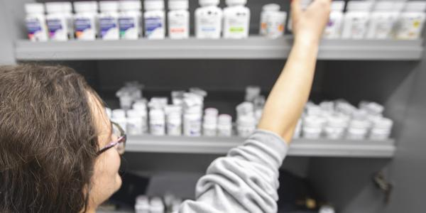 Pharmacist grabbing a pill bottle off the shelf