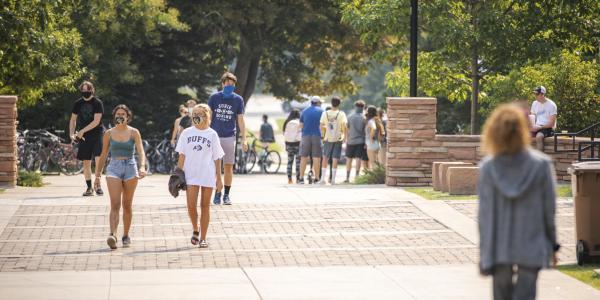 people walking through campus in masks