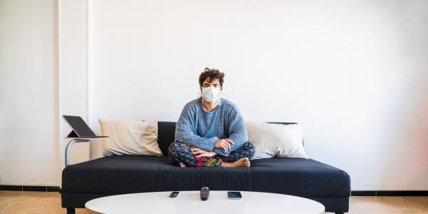student sitting alone on a couch in a mask