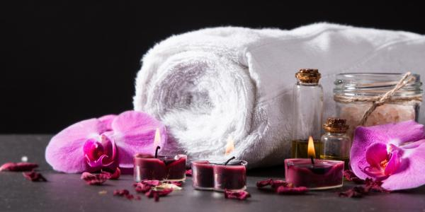 a rolled towel besides candles and flowers