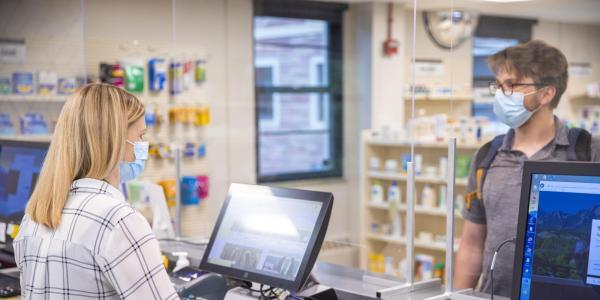 student at the pharmacist desk
