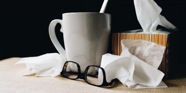 mug and glasses with tissues scattered around
