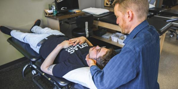 a provider adjusting the neck of a student