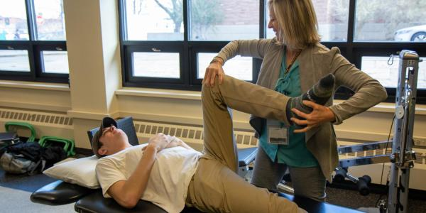 student getting their knee worked on by a physical therapist