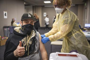 man in cu hat and sweatshirt giving a thumbs up as he gets the vaccine
