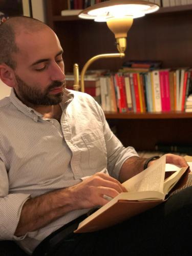Alex Priou reading by a bookshelf and lamp