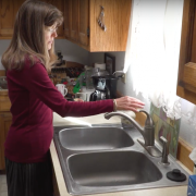 Woman near sink filling glass with water from the faucet