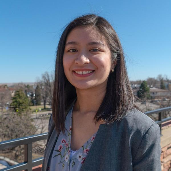 Alaynah Penalosa stands on a balcony with blue skies and trees in the background