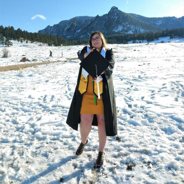 Kayleigh Cornell standing in snow with Boulder flatirons in the background