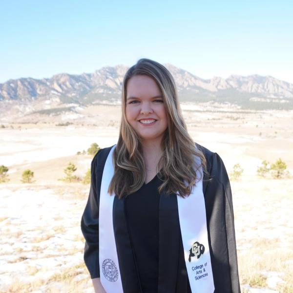 Kylie Conway wears her graduation gown and stands in a field of dry grass and snow with mountains in the background