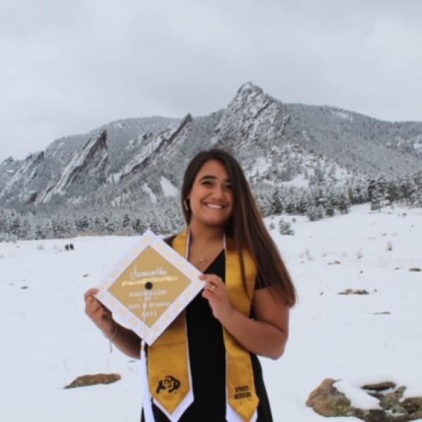 Sami Guneratne standing in snow in front of the Boulder flatirons