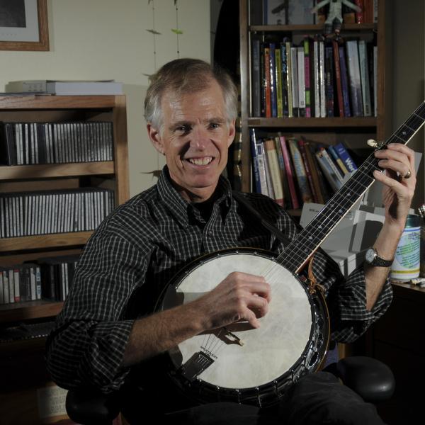 Daniel Jones playing a banjo in his office.