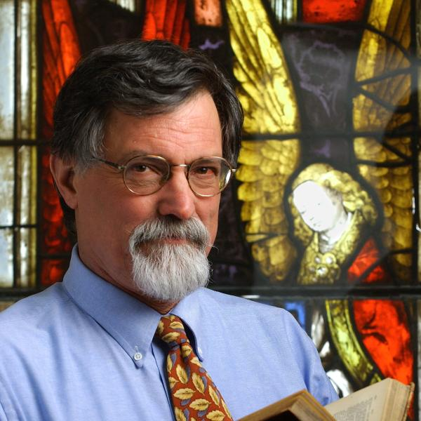 Dr. Christian Kopff in front of a stained glass window.