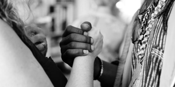 We stand in solidarity. Photo of black person and white person grasping hands.