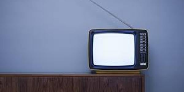 TV sitting on a table with blue background
